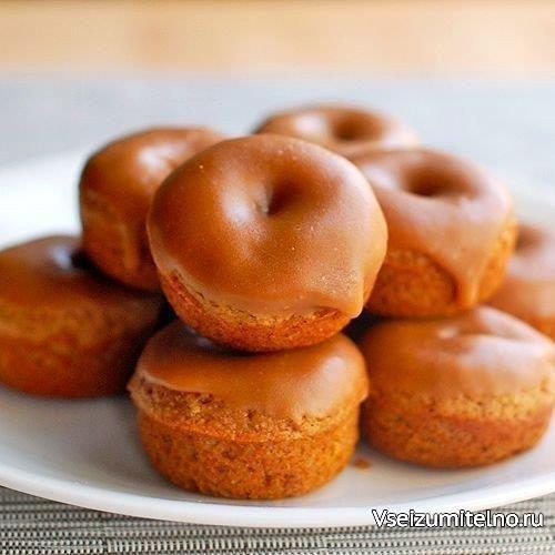 Имбирные пончики с глазурью  Ингредиенты:  Мука цельнозерновая - 1 ст.  Разрыхлитель - 1 ч. л. Сода пищевая - 0,2 ч. л.  Корица - 1 ч. л. Имбирь молотый - 0,5 ч. л.  Душистый перец - 1 щеп. Гвоздика молотая - 1 ч. л.  Соль - 0,2 ч. л. Сахар коричневый - 120 г  Куриное яйцо - 1 шт. Яблочный соус - 60 мл  Кленовый сироп - 2 ст. л. Молоко - 3 ст. л.  Масло сливочное - 4 ст. л. Сахарная пудра - 120 г  Приготовление:  1. Разогреть духовку до 175С. 2. Смешать в большой миске муку, разрыхлитель…