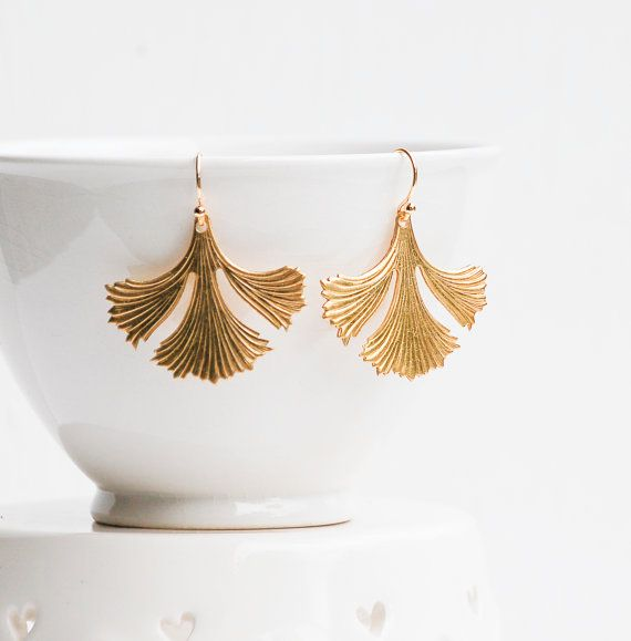 Delicate gold leaf earrings. These pretty golden raw brass ginkgo leaf earrings dangle from simple ear wires. Each earring measures approx 1 1/2 inches from the top of the ear-wire to the bottom of the leaf. The ginkgo leaf symbolizes peace, hope, and longevity.  Historically, the long-lived ginkgo represented strength and longevity to the Japanese. This symbolism became even more poignant after four ginkgo trees survived the 1945 atomic blast of Hiroshima. Today the trees remain as remi...