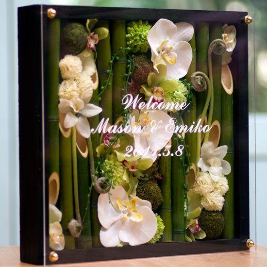 結婚式のウェルカムボードに竹の器に胡蝶蘭やシンビジュームを木枠に詰め込んだ、和ボード木枠白タイプです。