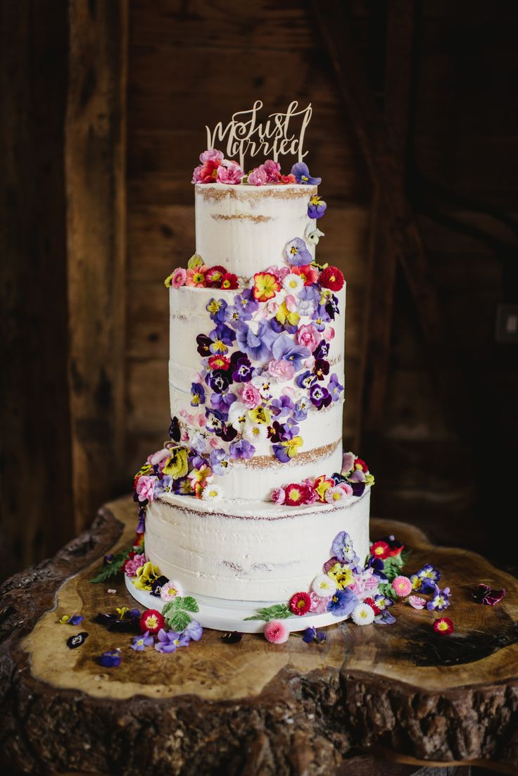 Semi-naked cake with cascading fresh edible flowers from Maddocks Farm Organics.