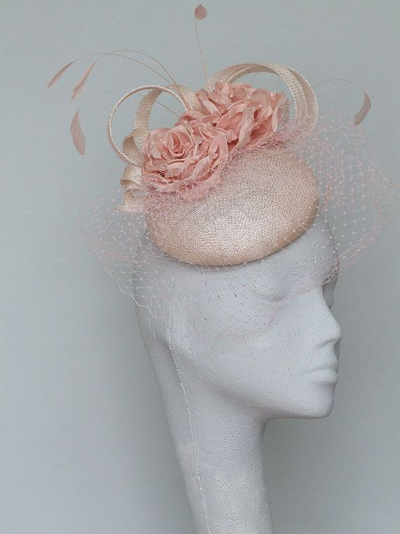 Hand blocked pale pink sinamay button fascinator. This lovely feminine headpiece is trimmed with hand made silk dupion flowers, sinamay curls and feathers and a delicate pale pink birdcage veil. Secured by hat elastic which is easily hidden.  Base 14cms 5.5 Fine for Royal Ascot  Please allow 5days for this item to be made.