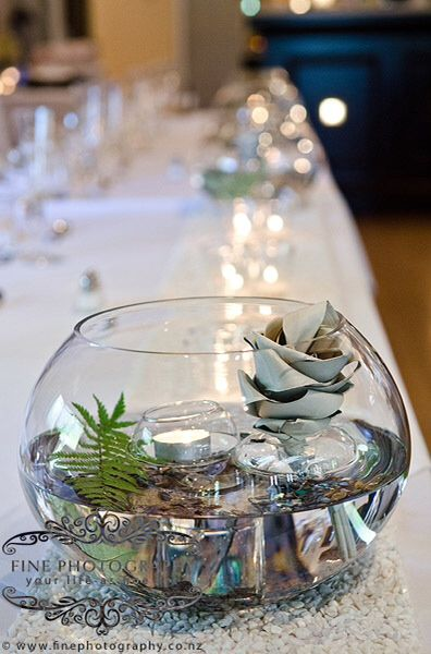 Side view of  centrepiece with fish bowl, water, paua pieces, fern and floating candle and flax flower.