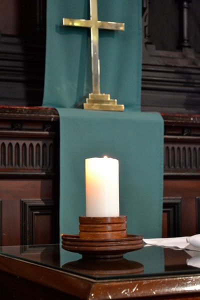 The Christ candle alight to signify the presence of Christ, the Light of the World.
