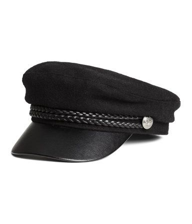 Black. Captain's cap in a felted wool blend. Braided band at front and metal buttons at sides. Lined.