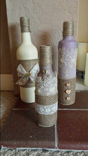 Old wine bottles painted and waxed with annie sloan paint and wax. Decorated with hessian craft ribbon, antique lace, twine and charms.