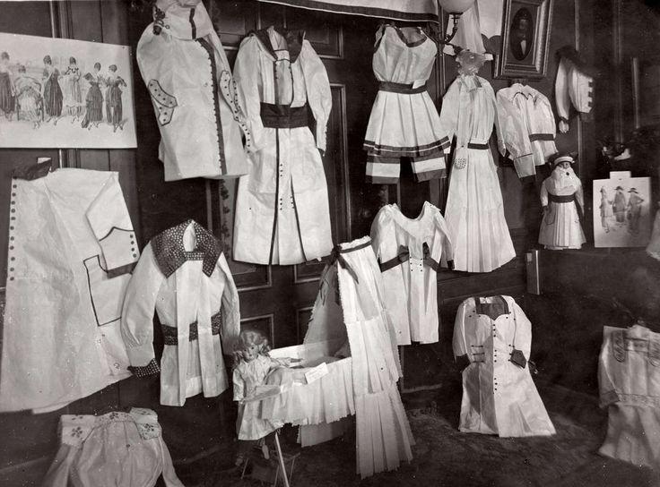 Naaien. Tentoonstelling papieren modellen van kleding en een wieg waar knippatronen van verkocht worden. Nederland, Amsterdam, 1918.