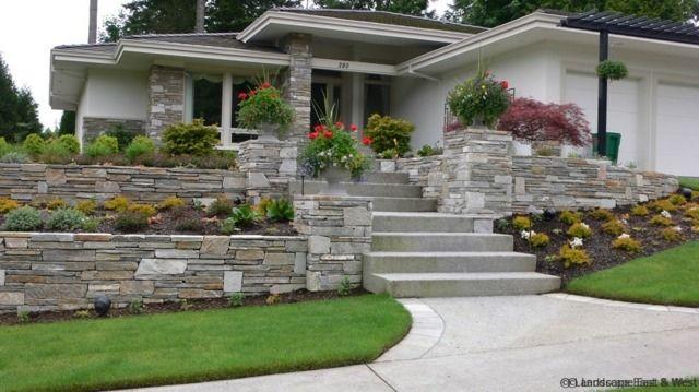 Une vue d'une belle maison et un mur en pierre naturel