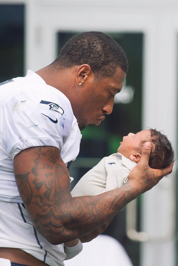 Man and baby, hot. Football player holding a baby, hot. Seahawks' Bruce Irvin holding a baby.. g'lawd!