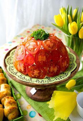 Tomaatinsiivuilla kuorrutettu voileipäkakku on kahvipöydän väriläiskä. Punaisen pinnan alta löytyy meetvurstitäyte ja kokojyväleipää. Charlotta kannattaa valmistaa jo edellisenä päivänä. Näin maut eht