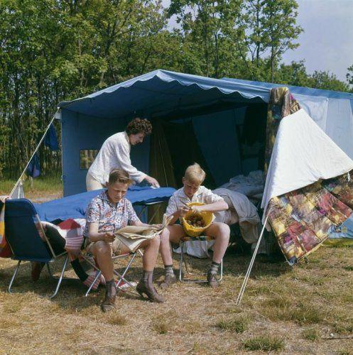 Kamperen met de bungalowtent. Moeder maakt het luchtbed schoon, een slaapzak hangt over een scheerlijn. Terwijl de ene zoon aardappels schilt, leest de ander een krant. Nederland, ca.  1964.