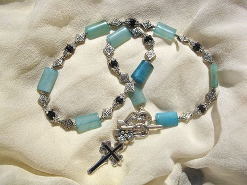 "Perfect to promote a positive attitude: Soft-blueish/green Jade is interspersed with Black Agate beads that are encapsulated in silver-coloured beads. This beautiful necklace measures approx 19"" and has an eye-catching front floral clasp with a sterling silver Saint James cross hanging below, inlaid with finest Azabache jet from Asturias."