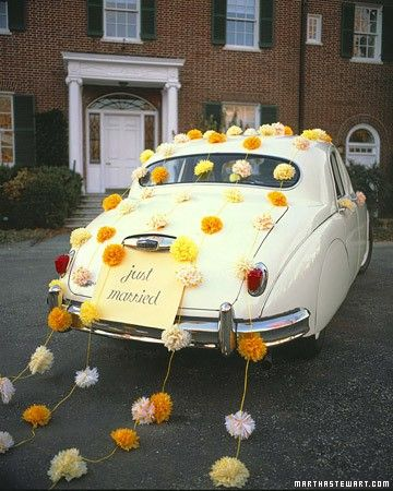 tissue paper and twine flowers wedding reception getaway car, and they stay on the car with suction cups, which won't damage the auto's exterior.