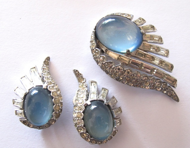 """Lovely deco dress clip and earrings , pale blue cabochons are surrounded by clear stones set in rhodium plated setting. In excellent condition, minimal wear to the back of the dress clip and one earring. No dark stones. Dress clip is 1⅝"""" by 1"""". Clip on earrings are 1⅛"""" by ¾"""".  Matches #103 on this site. #239"""