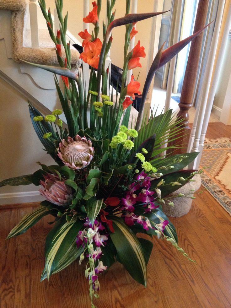 Protea, birds of paradise, orchids, calla lilies, button mums, and gladiolus.