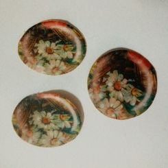 The picture are fabric cabochons that made. The printed fabric was attached with glue to a felt circle  then some polyester stuffing was inserted to it.