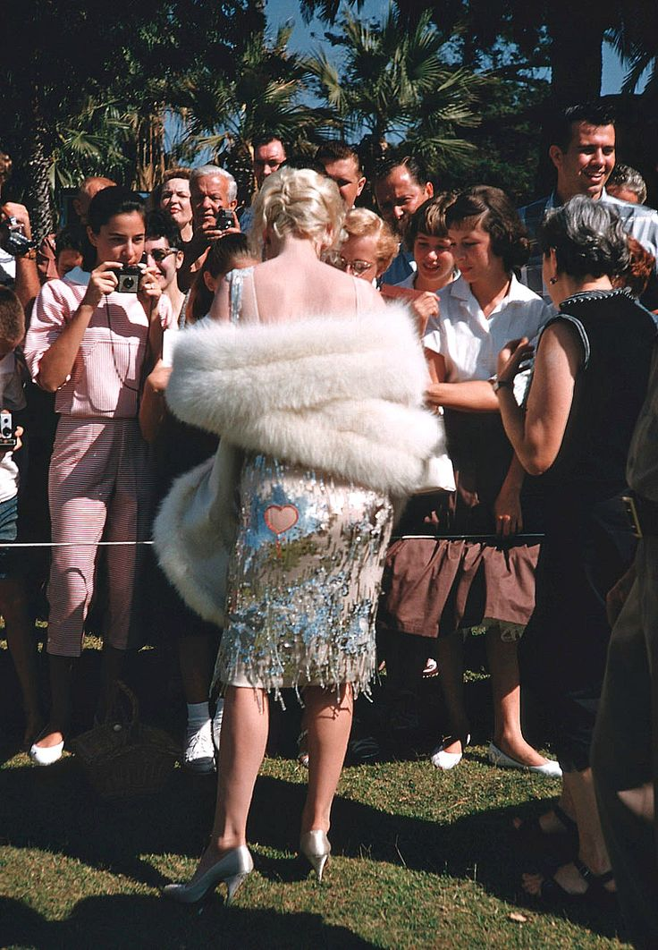 Marilyn Monroe photographed by Richard Miller signing autographs for fans on the set of Some Like It Hot, 1959.
