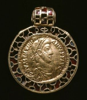 This pendant goes back, probably, to the 7th century AD, but the coin inside is a Roman Solidus showing the face of Emperor Valentinian II from the 4th century AD.