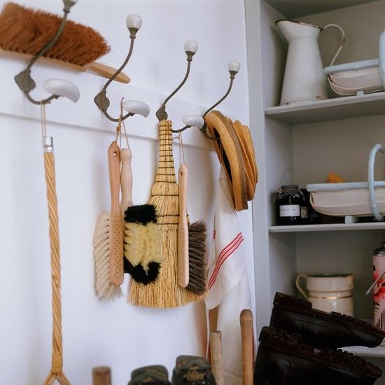 Hanging space  Large French coat hooks make the most of wall space and house brushes and cloths, while trug baskets on shelves built into an alcove provide a place for other odds and ends.