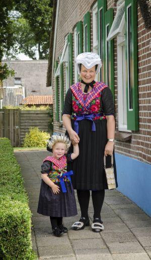 """""""Staphorster goed hoort gewoon bij mij"""" -  Margje Haasjes-Hokse (43) loopt als een van de jongste Staphorster vrouwen nog dagelijks in klederdracht; 's zomers alleen op zondag. Dochter Marlize (2) draagt één keer in de week het """"Staphorster goed."""" Beeld Niek Stam"""