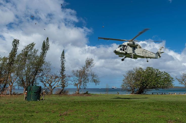 A SH-2G Sea Sprite helicopter transports a water tank from HMNZS CANTERBURY to the Lamen Bay school on Epi Island in Vanuatu.