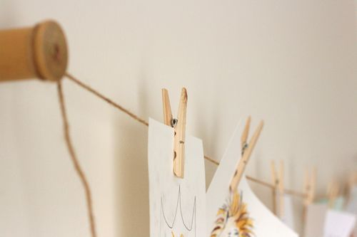sweet clothespin display for kids art. I love the vintage wooden spools and twine.