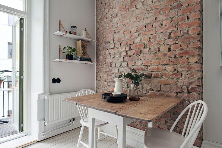 Ściana z czerwonej cegły w kuchni z białymi krzesłami i drewnianym stołem