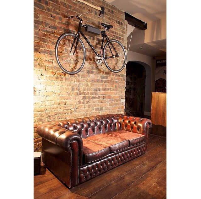 Brown sofa and decorative bike on the wall, with wooden flooring.   Barbers waiting area.