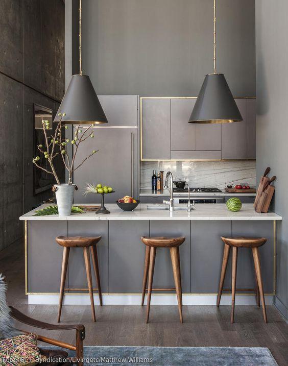 Eine rold gerahmte Küchenzeile wirkt neben dunklen Farbtönen sehr edel und dennoch modern. Das Thema wird auch in den dunklen Hängeleuchten geschickt aufgegriffen, für den natürlichen Touch sorgen die stilvollen Barhocker aus dunklem Holz.