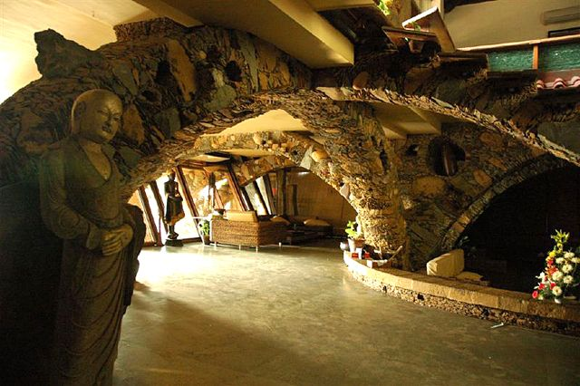 Interior view of the intersecting stone arches made from a variety of chipped stones, large boulders, and terracotta pots   Archnet