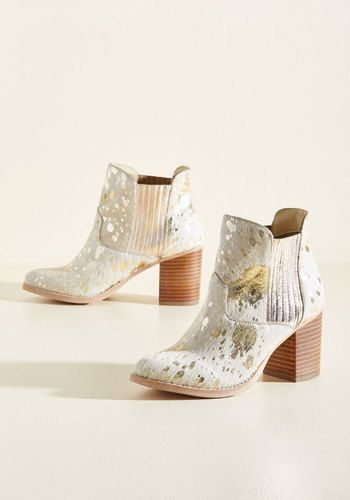 Who says statement-making style can't double as a wardrobe essential? These ivory booties - with their hair-on-hide uppers, gold foil paint splatters, and stacked heels - offer a look so strong, you'll wonder how your powerful gait ever got along without them!