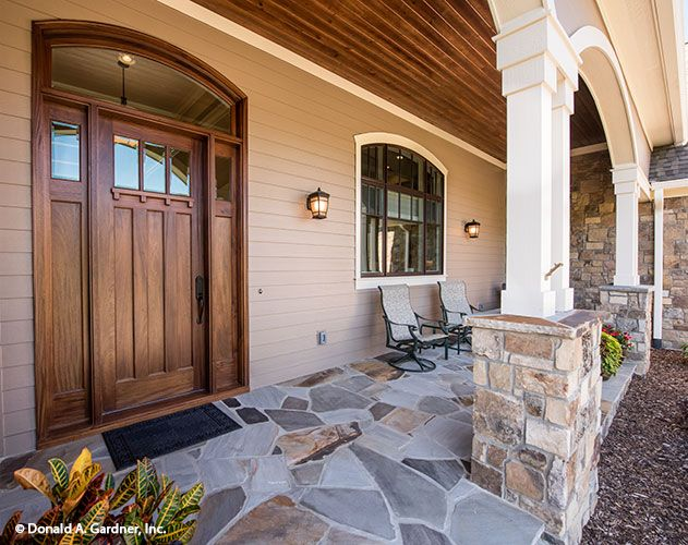 This front porch is so inviting with an arched and columned entry and the stately front door. The Chesnee house plan #1290.
