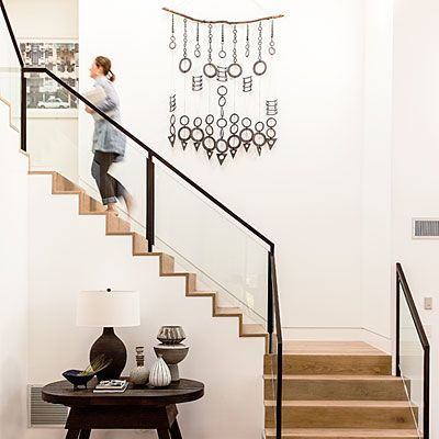 """The double-height entry creates a lot of drama—and wall space. Schrock and Dick filled it with a ceramic wall hanging and designed the staircase with sheets of glass in place of balusters. """"The glass fades out, so it's all about the artwork,"""" Dick says"""