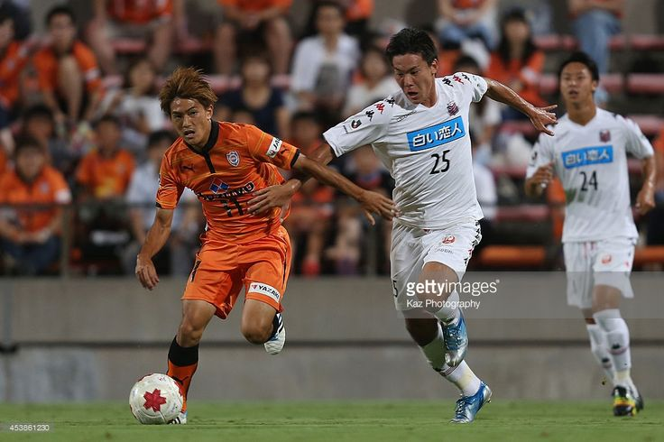 Kazuki Kushibiki of Consadole Sapporo and Toshiyuki Takagi of Shimizu S-Pulse compete for the ball during the Emperor's Cup third round match between Shimizu S-Pulse and Consadole Sapporo at IAI Stadium Nihondaira on August 20, 2014 in Shizuoka, Japan.