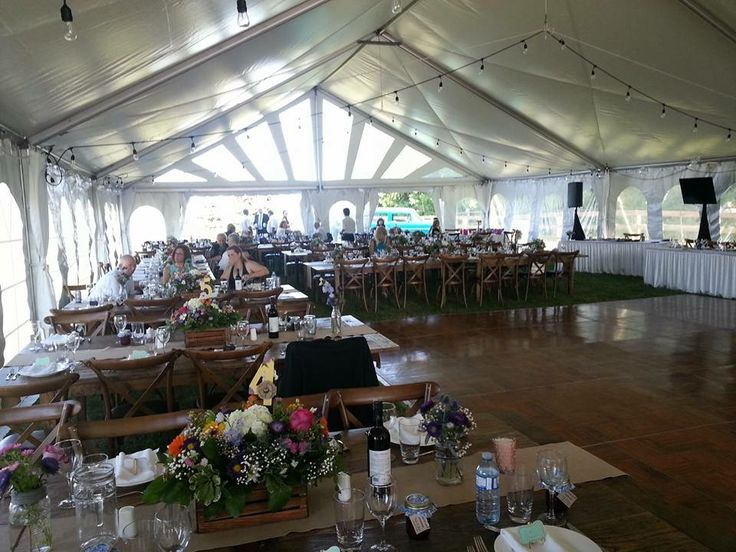 Large tent, wood harvest tables, lots of flowers