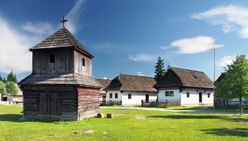 Rare wooden bell tower with folk houses in background. These preserved constructions are located in open-air museum of Liptov Village, Slovakia. This open-air museum shows typical folk architecture of Slovak rural communities and their life-style from 14th to early 20th century.