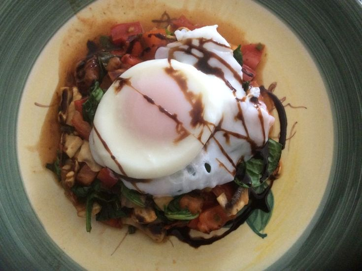 A delicious breakfast of spicy mix of mushroom,tomato and spinach topped with a poached egg and a swirl of balsamic.