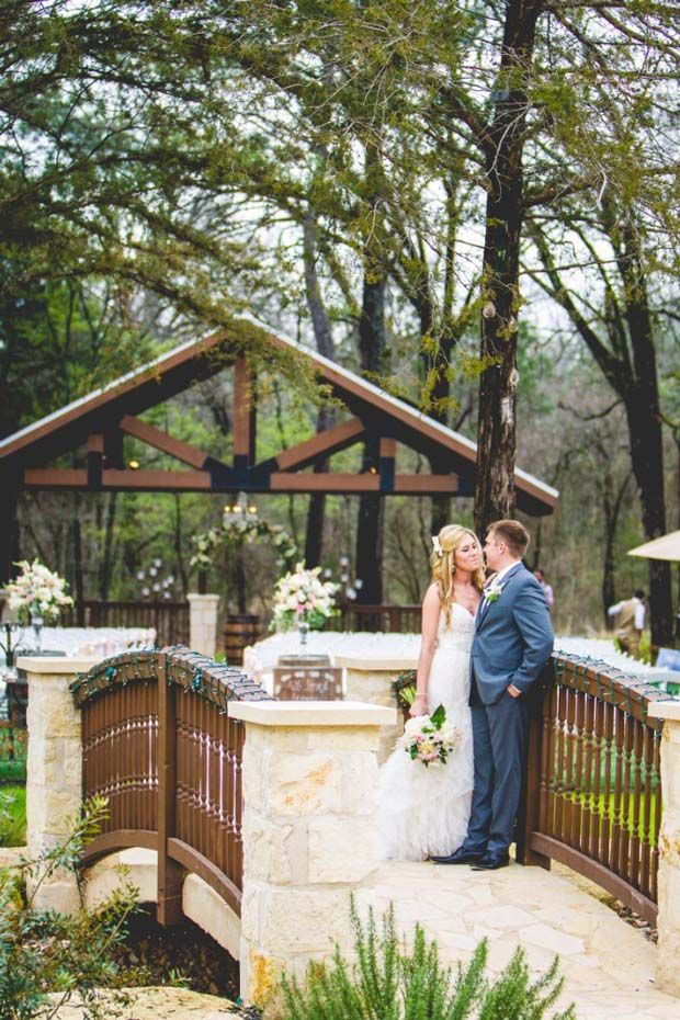 Romantic interlude between bride and groom as they embrace on the charming wood and stone bridge at The Springs in Rockwall / Dallas wedding venues