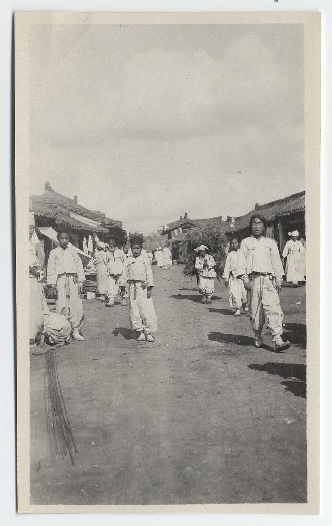 [A Korean boy with two-storied hat ] a busy street, including a young boy and a coolie. The boy wears a two-storied hat formerly reserved for use by Confucian scholars. The hat was probably owned by his ancestors. The coolie, or laborer, carries a full bale of hay in an A-frame carrier on his back. 1904. Willard D. Straight/Early U.S.-Korea Diplomatic Relations, Cornell Univ Library
