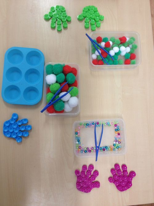 """The activity has been created to support fine motor manipulation & is differentiated over three levels...  The hands are shower stickers & (bought from 'B+M Bargains'). The children use their fine motor skills & a pair of tweezers to move the beads from the tray to the little pockets on the hands. The children with less well developed skills pick up the pom-poms & put them into the larger dish shaped containers ("""",)"""