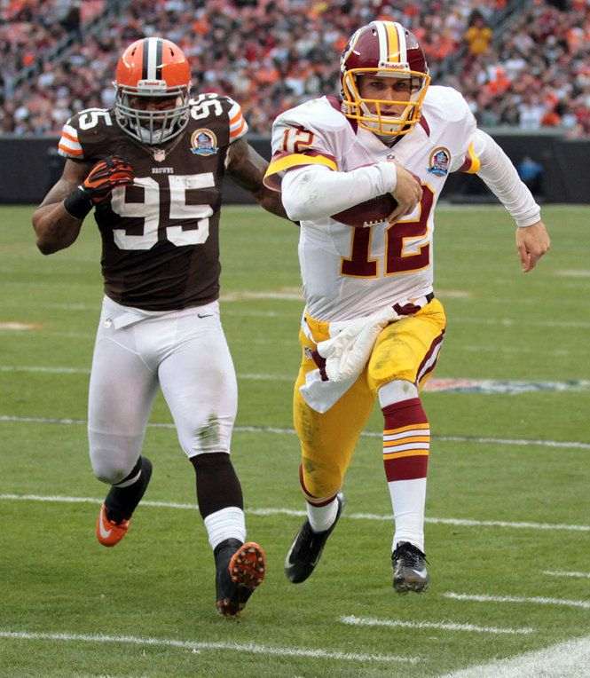 Washington Redskins quarterback Kirk Cousins runs for a first down as he is driven out of bounds by Cleveland Browns defensive end Juqua Parker in the second half Sunday, December 16, 2012 at Cleveland Browns Stadium in Cleveland. The Browns lost the game 38-21. (Joshua Gunter/ The Plain Dealer)