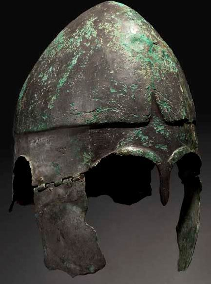 Chalcidian helmet, type V, early 4th century B.C.  The lower section embellished with contoured ribs in repoussé at the ear and eye cut-outs. A lancet-shaped nose guard between the eye brows. Behind the ear cut-outs, the rear section features a shallow fuller before terminating in a short neck guard that curves outwards. The cheek pieces are attached to the skull by a five-part hinge, with two bushings for each cheek piece, 29 cm high. Private collection, from Hermann Historica auction