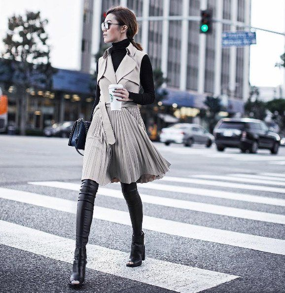 A trench coat vest over a turtleneck top and over-the-knee boots.