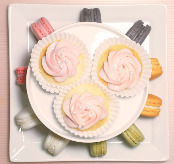 5 Flavored macarons with vanilla frosted cupcakes.