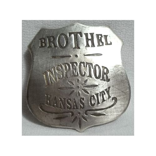 """The badge is a shield and is made of solid copper and double die struck with a silver-plated antique finish . It measures 2 inches across and has a pin for attaching to a shirt. It reads """"Brothel Inspector Kansas City"""". This was an official job title at one time and there were laws regulating the brothel industry."""