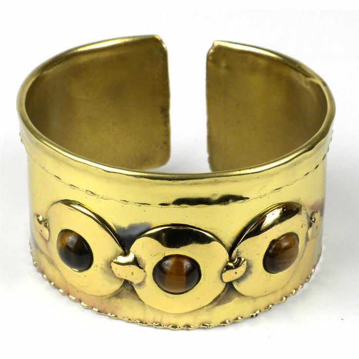 Handcrafted by South African artisans, this brass cuff with a ruffled edge is accented with disks of brilliant brass and three tiger eye stones. The feathering on this 1.75-inch bracelet is achieved by applying extreme heat rather than paints or dyes.