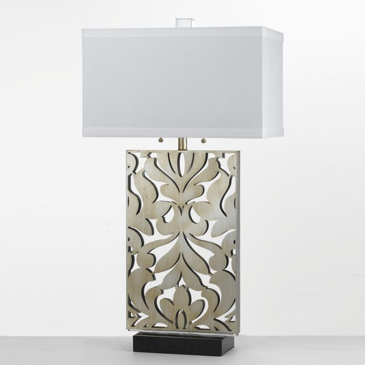 Our Daydream table lamp is pared down to look fresh and modern, yet it continues to have a familiar nod toward tradition. When illuminated, the table lamps light rakes across the surface of this design. Creating shadows and surface details. Crafted in laser cut metal, the table lamp is finished in Glint that is a hand applied silver finish. The laser panel sits over a black base glowing light to shine. The shade is crafted in a white poly silk with a 1 inch welt on the top and bottom.