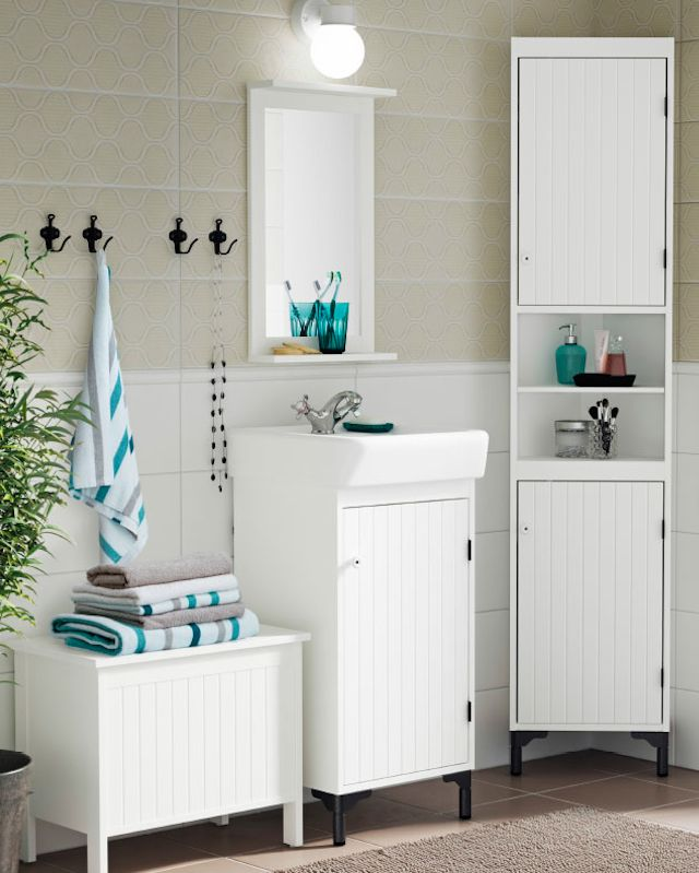 ikea country bathroom in white and grey with silvern sink cabinet and corner storage in white