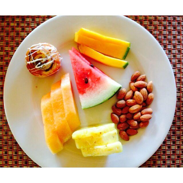 My healthy breakfast: watermelon, mango, cantaloupe, pineapple, small Danish pastry, and almonds.