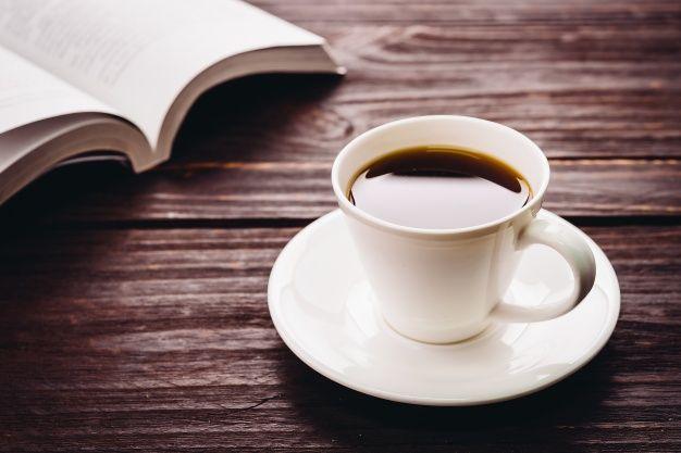 Чашка кофе на деревянный стол и книги Бесплатные Фотографии
