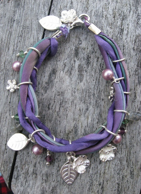 Purple and abalone-dyed silk cords, silver charms, Swarovski pearls and crystals, and labradorite disks